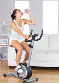 Cute fit woman drinking water while training on an exercise bike in her living room